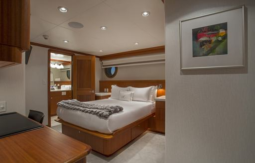 Double bed in cabin on explorer yacht MARCATO, with wooden detailing and door to ensuite open