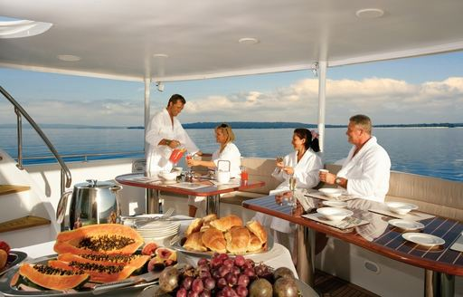 charter guests enjoy a delicious breakfast on sundeck of superyacht 'Emerald Lady'