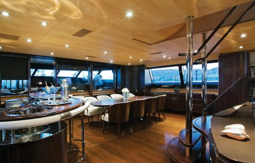 Interior dining layout onboard Parsifal III, long table adjoined by staircase and wet bar, facing wide reaching windows