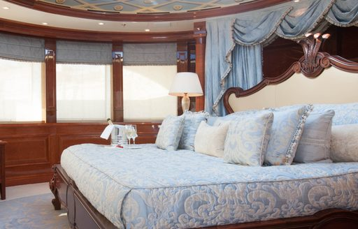 benetti superyacht st david master suite with bed with blue detailing and palatial headboard