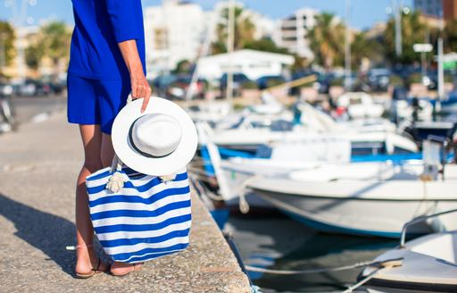 a woman in blue holds her hat and a tote bag full of the essential things she needs to enjoy a day in the sun while on her luxury yacht charter in Italy