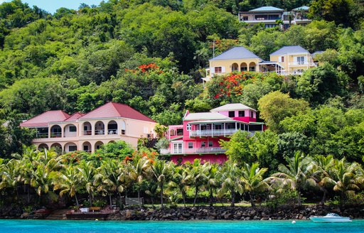Brightly-coloured houses by the sea as seen from a luxury yacht charter in the British Virgin Islands
