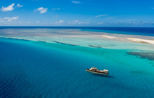 aerial view of luxury motor yacht over the rainbow off the coast of East Africa surrounded by bright blue seas with sand bar in background