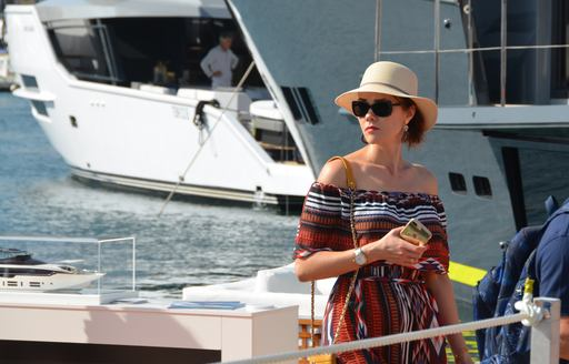 Well-dressed woman poses on yacht at boat show in Cannes