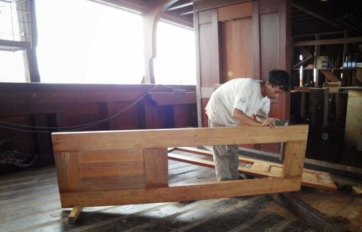 A master carpenter constructs a door for luxury phinisi Dunia Baru
