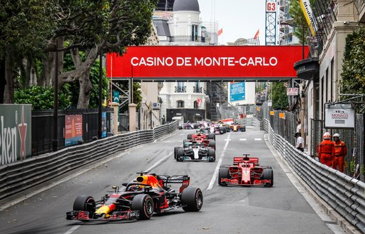 Head-on view of racecars as they speed down the track below Monte Carlo banners at the Formula One Monaco Grand Prix