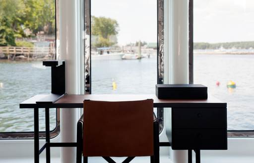 A dark wood chair tucked beneath a desk which looks out across the ocean from inside a superyacht