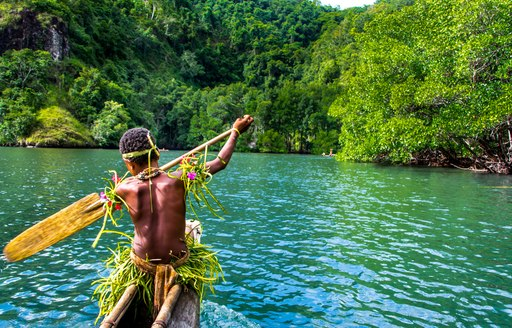 Man rows boat in Papua New Guinea