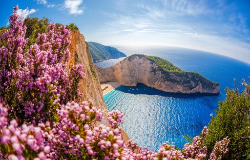 Bay in Greece with pink flowers in foreground, the ideal superyacht chartr vacation