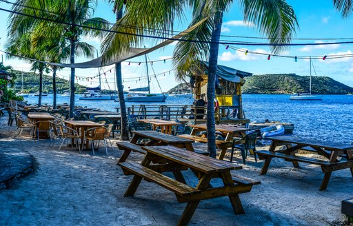 Tables and chairs of a restaurant on the beach in the Virgin Islands, with palm trees and sea in the background