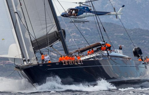helicopter flies above charter yacht PERSEUS^3 as she competes in the Perini Navi Cup