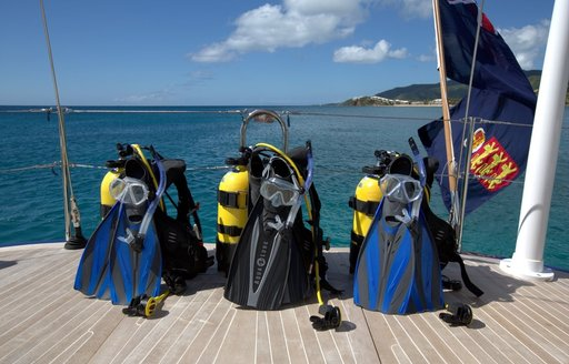 scuba diving equipment lines up on swim platform of luxury yacht PTARMIGAN