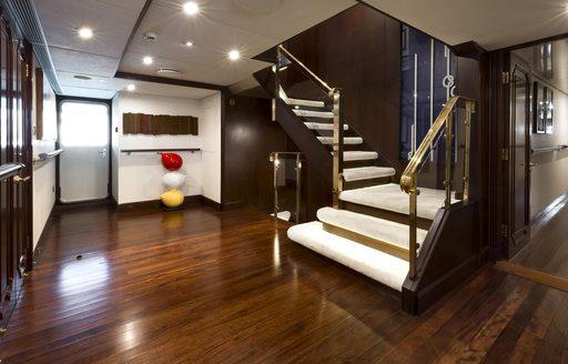 Staircase leading down into elegant lobby on Superyacht CHAKRA