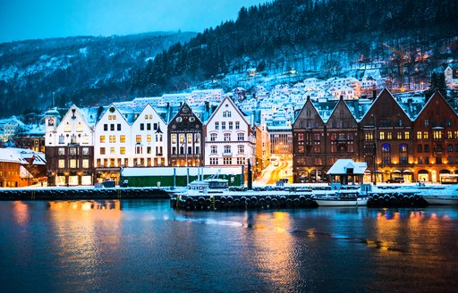 snowy houses by the water in norway