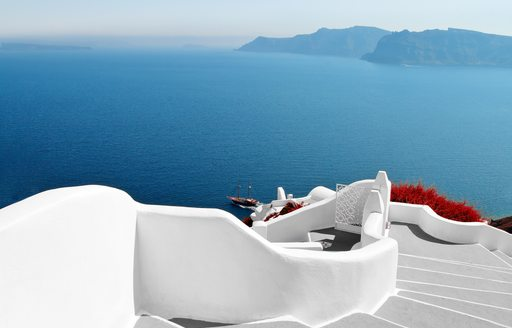 Town of Santorini in greece with white steps and red flowers