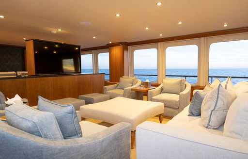 Comfortable skylounge with seats facing TV on superyacht ZEAL