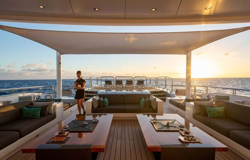 the aft skylounge of a superyacht with a lovely crew member taking every bit of caution during this pandemic so the guests of a luxury yacht charter have a relaxing and stress free vacation