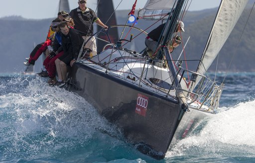 close up of sailing yacht cutting through the water as part of the Audi Hamilton Island Race Week
