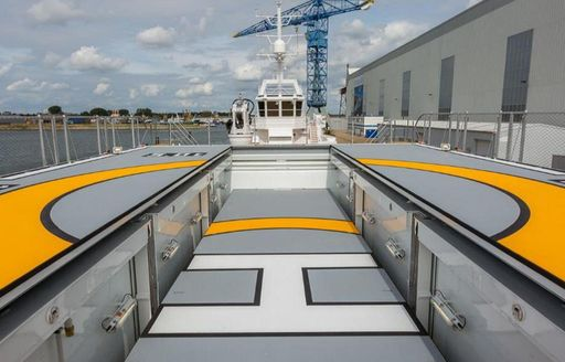 Helipad on Game Changer yacht with crane in background