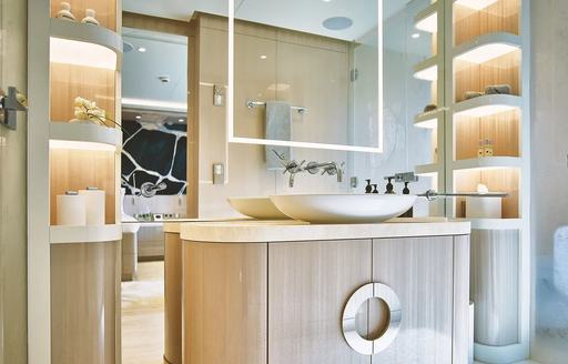 luxury yacht soaring en suite bathroom with backlit shelves and mirror showing guest cabin in background