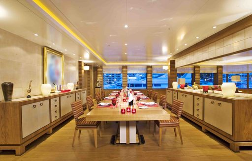 A formal dining table positioned in the centre of an image of the interior of superyacht 'Lady S'