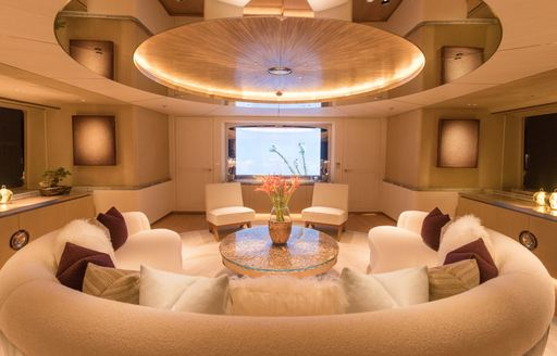 Lounge area on charter yacht DRIFTWOOD with circular sofa and gold light fixture above