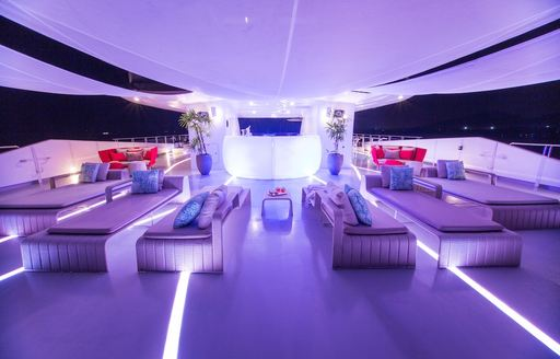 Lit up sun deck of SALUZI with seating and jacuzzis on board charter yacht SALUZZI