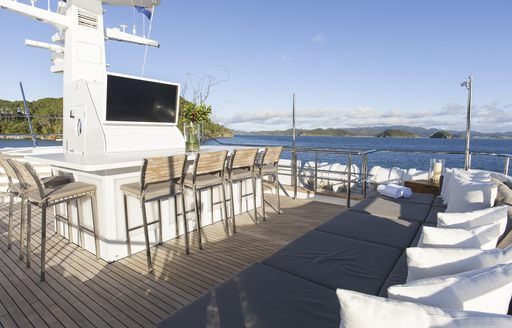bar with TV and bar stools on the sundeck of luxury yacht RELENTLESS