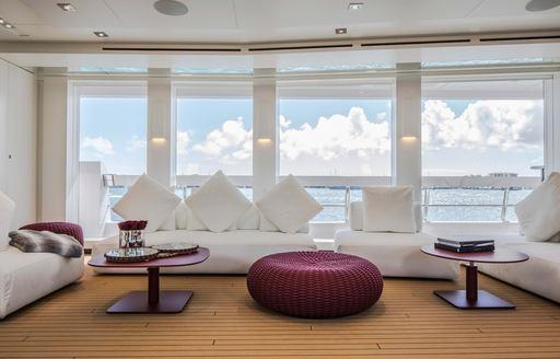 the luxurious seatig arrangement inside the upper deck salon of charter yacht home overlooking the Caribbean water