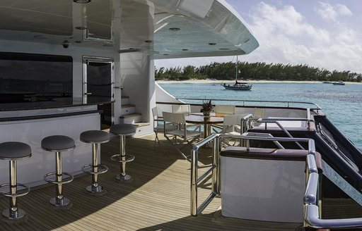 Bar and seating on covered deck of superyacht M3
