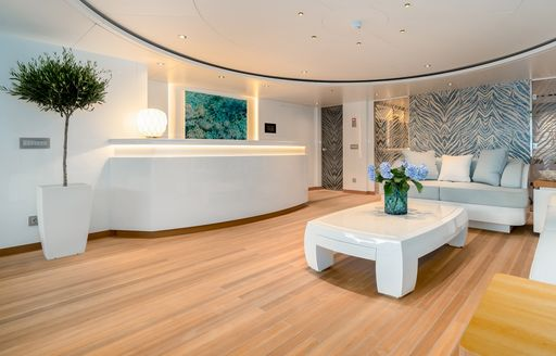 Open plan room on superyacht O'PARI, with white furnishing and teak decking