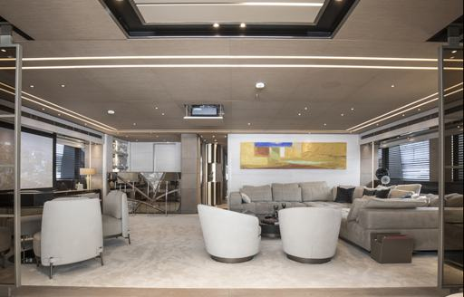 Lounge area on superyacht SEVERIN'S with sofas and chairs facing large TV on wall