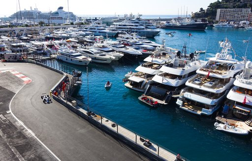 F1 car on the circuit during Monaco Grand Prix, tearing past yachts in the marina