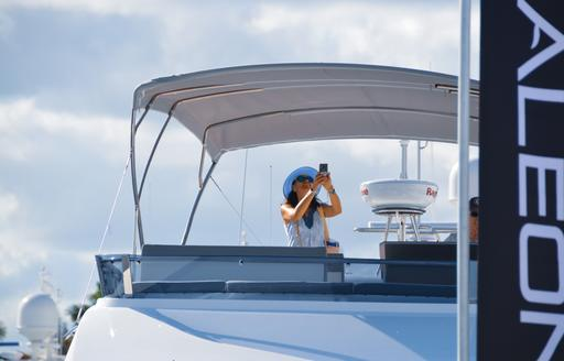 Woman captures image at FLIBS from sundeck of yacht