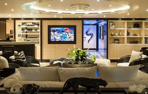 Lounge area on superyacht Sea Rhapsody with artwork on wall and sculptures visible