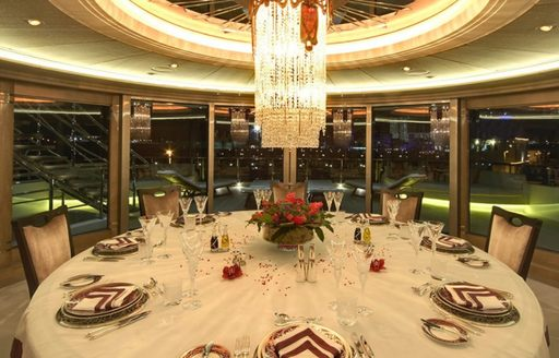 Formal dining arrangement onboard yacht charter AMARYLLIS. Round table ornately displayed with hanging chandelier directly above, surrounded by extensive windows.