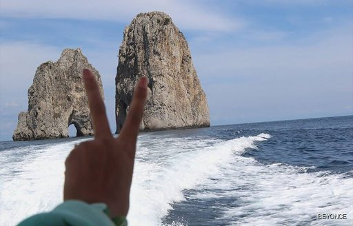 Beyonces hand with oceans and rocks in background from the deck of superyacht KISMET