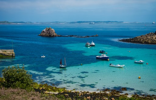 beautiful blue water of the scilly isles, with sandy seabed and little boats bobbing on the water