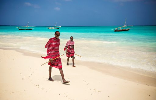 men wearing traditional swahili outfits walk on beach in tanzania
