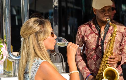 Woman enjoying champane on board superyacht with saxophonist in background at Monaco Yacht Show 2018