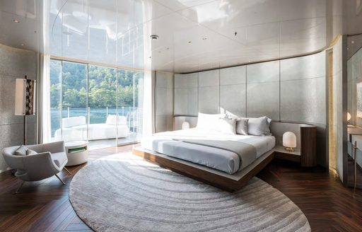 Lightly colored bedroom on superyacht SAVANNAH, with large window looking onto patio