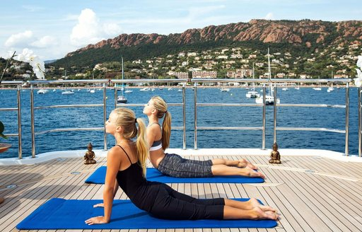 Charter guests do yoga on deck of luxury yachtMy Seanna