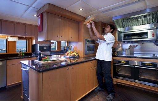 yacht chef flips pizza in galley