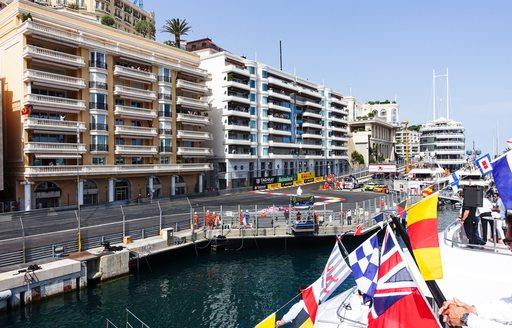 Dockside view of Monaco Grand prix track, line of Row of superyachts moored at Monaco Grand Prix