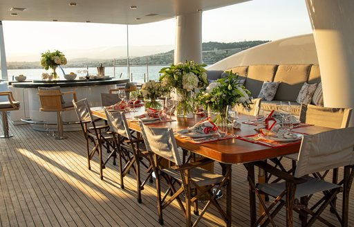 sundeck on luxury yacht spirit, with large dining table and bar with barstools