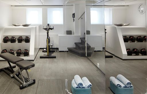 the fully equipped gym in charter yacht HOME with windows and large mirror