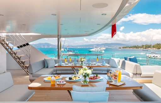 seating areas set up for breakfast on the aft deck of a superyacht