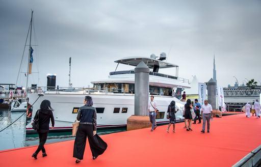 visitors stroll the red carpet boardwalk at the Dubai International Boat Show