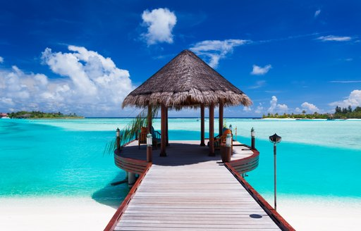 Wooden pier stretching out over turquoise waters in the maldives