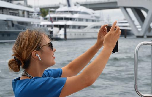 woman snaps picture of yachts at flibs